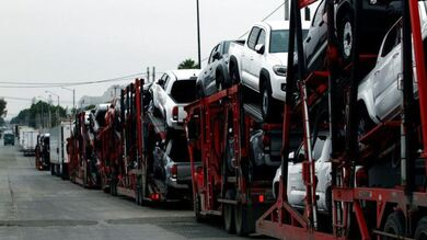 Un remolque transporta autos Toyota para su entrega mientras hacen cola en el control de aduanas fronterizo para cruzar a EU.